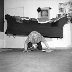 Glamorous strongwoman Joan Rhodes exercises her strength whilst tackling housework in her flat in Hampstead, north London, March 1958. (Photo by Ken Harding/BIPs)
