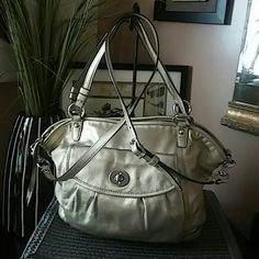 Authentic Metallic Leah Coach Tote Gold Silver!! Authentic Metallic Leah Coach Tote Gold Silver!! This bag is made out of gorgeous metallic gold leather  silver tone hardware. There is a flap pocket on the front and a open pocket on the back of the bag.  Light blue lining and features a zipper pocket, patch pocket, cell phone pocket. Missing tag.  Will add item in 3rd picture. dust bag.  In Great Condition!!  Firm. Coach Bags Totes