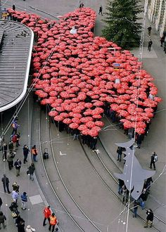 Umbrellas, Paradenplatz, Zürich, Switzerland - Members of Swiss trade union Unia hold red umbrellas while forming a large fish apparently swimming after a smaller shark in Zurich. The action was reportedly part of a protest against financial sharks.