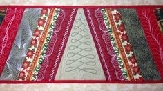 The strip pieced design of this Christmas table runner is a nice canvas for testing new free motion quilting designs.
