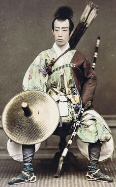 Samurai holding a yumi (bow) and wearing a yugote (shooting sleeves) over his left arm.