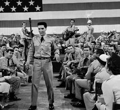 """The nation's new 50-star flag makes its film debut on July 4, 1960, as a backdrop for a movie by Paramount Pictures. Far too large ever to be flown, the 21-by-42 silk flag with 14-inch stars and 18-inch wide stripes was made up for this scene starring Elvis Presley, in Hal Wallis' """"G.I. Blues""""  ©Ho / AP"""