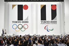 The official emblem of the Tokyo 2020 Olympic (left) and Paralympic Games is unveiled by the Tokyo 2020 Organizing Committee to a large crowed gathered in front of the Tokyo Metropolitan Government office on Friday night.