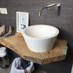 Moderes Aufsatzwaschbecken auf einer rustikalen Holzscheibe