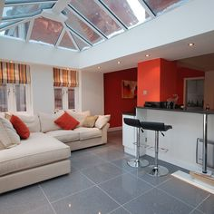 Modern orange & white orangery extension topped with a large glass lantern roof, with spot lighting around the interior ceiling pelmet. A new kitchen island separates the living area whilst retaining natural light and space. Extension Designs, Glass Extension, House Extension Design, Extension Ideas, Orangery Roof, Roof Lantern, Sky Lantern, House Extensions, Kitchen Extensions