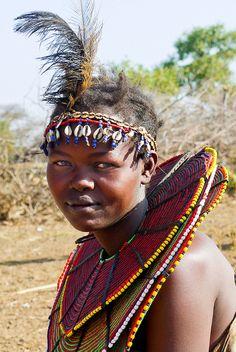 Kenya, Kenia, Pokot village, Pokot dorpje, Pokot people    Vrouwen en meisjes dragen typerende wijde kragen van riethalmen, geregen aan strengen van doum palmen. De kraag bedekt de schouders en een deel van het bovenlichaam.