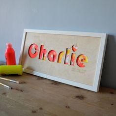 A great way to display kid's artwork - behind a plywood lasercut of your child's name