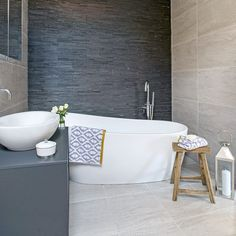 Slate clad bathroom with freestanding white slipper bath