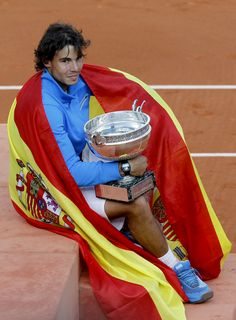 photo ... Spanish tennis player ... with a big trofeo and wrapped in the Spanish flag ...
