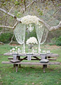 Glass beads hung from a tree for a photo backdrop. Long picnic table for court