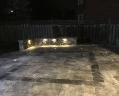Retaining wall and interlocking patio with landscaping lights.