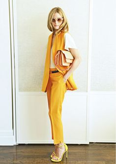 Olivia Palermo wears an orange matching suit set from Zara with a white t-shirt, yellow Stuart Weitzman heels, and a blush pink bag