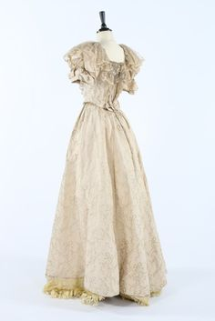 a silver and ivory brocade ball gown, circa 1895, woven with bows and foliage…