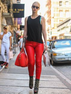 Australian rapper Iggy Azalea takes a stroll in NYC wearing a black sleeveless top over red trousers and gray lace-up ankle boots. She accessorized with a large red tote and large dark cat-eye sunglasses. via dailymail.co.uk