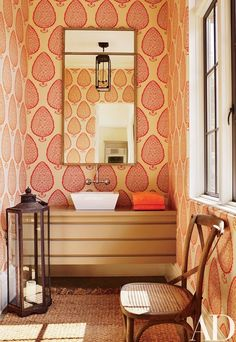 A Katie Ridder wallpaper from Holland & Sherry lines a powder room | archdigest.com