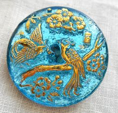 One Czech translucent aqua blue and gold glass peacock decorative shank button, 27mm, C02201