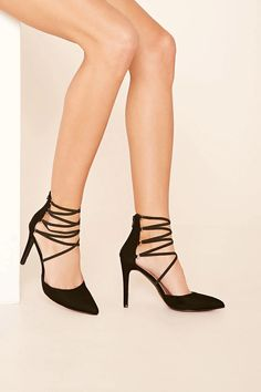 A pair of faux suede heels with a stiletto heel, a crisscross strappy banded front, and a back zipper closure.