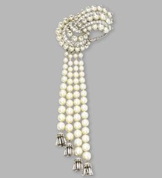 Platinum, cultured pearl and diamond tassel clip-brooch, Van Cleef & Arpels, circa 1950. The stylized bow supporting a fringe accented by diamond tassels, set throughout with cultured pearls measuring approximately 7.4 to 2.9 mm., and round, single-cut and baguette diamonds weighing approximately 6.50 carats, signed Van Cleef & Arpels, numbered N.Y. 14437.