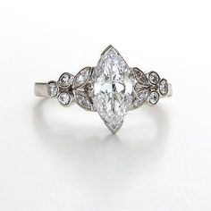 Center vintage marquise diamond weighs 1.23 carats D color and VS1 clarity with GIA report #2165027273. set in a beautiful platinum ring with a floral pattern of ten additional diamonds. This is an original antique engagement ring from the 1930s. Size 5.5. Resizing may be possible, please inquire. #R140423-1