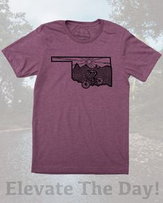 Oklahoma shirt with original mountain bike print by Milostees- Graphic illustration of a cyclist descending Bluff Creek for an epic ride. Hand screen printed art on soft plum tee in a cotton, polyester blend that is perfect for causal wear in Oklahoma City or riding Turkey Mountain. Elevate the day wear a more comfortable you! $21.99, free shipping in the USA. #OklahomaShirt #MTBShirt