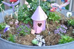 Love the clothesline and little rain boots in this fairy garden! House made from dollar store bird house.