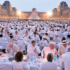 Dinner in white at the Louvre, Paris. The Dinner en Blanc in France is an organized outdoor picnic that operates like a flash mob. The groups will show up at a set location that they won't know until an hour beforehand where they will be headed. They set up tables, set out elegant food, silverware and toast the season. Just as quickly as they arrive, the group dissipates, leaving no trace.