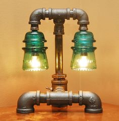 We have some of these Green Glass Insulators...always wanted to do something cool with them. Industrial Style Pipe Lamp with Green Glass Insulators