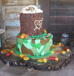 """This is a groom's cake for a hunter. The """"log"""" is covered in chocolate icing. The camouflage icing, antlers (on top of the log), the leaves and shotgun shells are fondant. On the top of the bottom layer in front of the log, it says """"The Hunt is Over."""""""