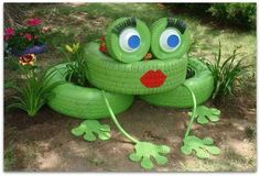 Recycled tires painted green and arranged into a frog with flowers planted inside the tires.