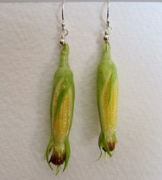 3.5 x .5 x .5 cm  Dangling from French ear wires, these ears of corn or ready to shuck and be buttered!  Each piece of corn is permanently set with sterling silver and given a water-resistent protective coating that will ensure years of wear. On