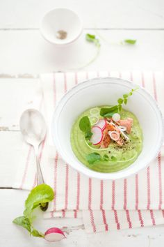 a soup made of avocados, cucumber and apple served with poached salmon, radishes, and watercress. mmmm