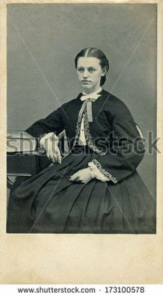 Circa 1861. Young pioneer woman dressed in Victorian style clothing from the Civil War era. Her dress has pagoda sleeves with a hoop skirt. You can purchase a digital version of this photo at the above web link.