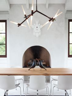 Barbara Hill designed this modern home in Atlanta, Georgia. Its informal dining space has a slightly rustic feel, sporting bronze and wood in the form of a Lindsey Adams Adelman chandelier for Roll & Hill.