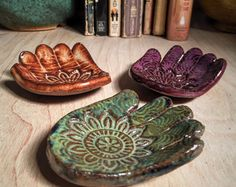 These eclectic little dishes can be used as a ring dish, spoon rest, incense holder, tea bag rest, little soap dish and a dozen other uses. 2 1/4 inches wide and 3 inches long, glazed rusty golden brown with a light wood texture and a lovely rustic mandala pattern stamped into the palm. Each dish has minimal color variations.  These would make lovely little party/shower/wedding favors. Message me if you would like to place a custom order with other color or texture options and I will send…