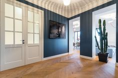 Le bleu profond réchauffé par le ton miel du parquet chêne ainsi que le jeu d'ombre et lumière de la suspension Vertigo créent une ambiance feutrée à cette vaste entrée. wwwstudiopfid.com