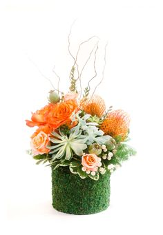 For those who are truly down to earth, succulents, Free Spirit roses, hypercium berries, poppy seed heads and pincushion protea spring forth from a moss-covered vase.  From Free Spirit Floral via @BloompopHQ