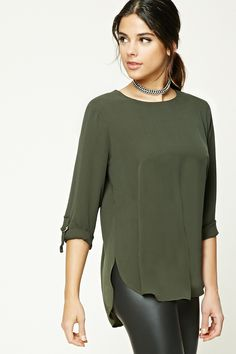 A textured woven top featuring an exposed zipper back, 3/4 sleeves with adjustable cuffs, high-polish accents, side slits, a dolphin hem, and a longline silhouette.