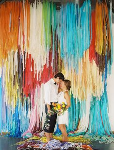 10 Unique Statement Walls for Your Wedding Decor | Can't pick just a few shades for your color palette? This bride creatively strung dip-dyed colors of fabric for her backdrop. Use rich and vivid decor pieces to brighten your special day.