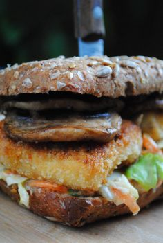 Epic tofu burger with salad spicy mushrooms and oven baked potato strips.