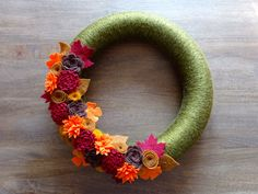 """This beautiful fall felt wreath is 14"""" and has been wrapped in a soft two-toned green yarn and designed with hand-made felt flowers and"""