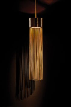 Berti Solid Brass & Glass Pendant - The Berti Pendant from Arteriors Home was inspired by sunlit grass blowing in a field. It glows through a frosted glass lens in the center of a straight fringe of narrow brass threads, falling downward from a cylindrical base. $2,016