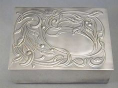 Manufacturer unknown, Designer 	unknown, Silver plate Art Nouveau cigarette box with floral decoration to lid and a wooden lining, unmarked, Probably German, c.1905 http://www.titusomega.com/Object%20Profile%20and%20Photos/Old%20profiles/Metalware/Art_nouveau_cigarette_box_seeds.htm