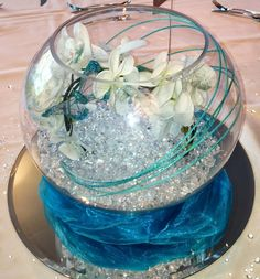 Table Centrepieces, something similar to this is what we talked about maybe adding some water and some food coloring to change the color of the water..and if not flowers in the bowl some kind of floating candle, or a arrangement on top of the bowl but here is an idea :))