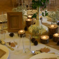 Kilver Court Wedding Fair, Rustic and Autumnal centrepiece with log tea lights, pine cones and gypsophila in jam jars wrapped with twine- Styling by Elizabeth Weddings