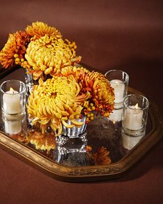 Orange and bronze football mums displayed on glass mirror accented with tea lights