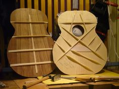 Top and back bracing of an acoustic guitar.  Looks like a rather large body for this one: possibly a Jumbo or an SJ size.  There are a few variations from a traditional Martin-style bracing pattern:  No Popsicle brace; the upper tone bar goes into the brace for the bridge; the finger braces appear spaced a little farther apart than normal.  Also, the X-braces appear to be at 90 degrees.  Usually the angle is less, so that the X-Braces extend farther vertically along the top.