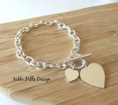 This custom handcrafted Silver Heart Bracelet is a Tiffany inspired design by Nikki Hills Design on Etsy. A bracelet for everyday wear, perfect on it's own or layered with other sterling silver bracelets for a modern stacked look. It would also make a special birthday gift, maybe for a 30th or 50th Birthday Celebration or an Anniversary Gift for your Wife or Girlfriend. Christmas is coming. Imagine her face as she unwraps the gift box to reveal this beautiful bracelet…