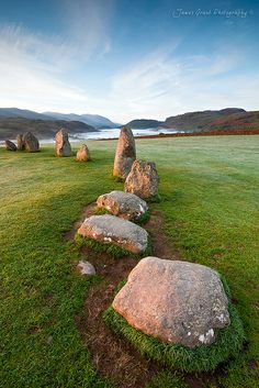 Castlerigg Stone Circle near Keswick in the Lake District is one of the most atmospheric of henges in Britain. The silvery white seen beyond the edge of the green hilltop is not water but more likely valley mist as the land drops away very abruptly on all sides of the circle's hilltop.