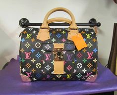 This colorful arm bag features gold hardware, tan handles, and a multi-color body to match any outfit. Pre-owned Louis Vuitton.