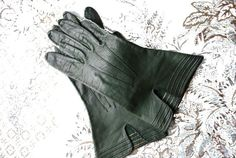 Luxurious vintage 60s forest green genuine kid gloves with a pin tack embroidry. Size 6.